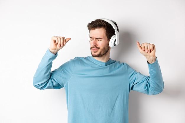 Jovem feliz se divertindo em fones de ouvido, dançando enquanto ouve música em fones de ouvido sem fio, fundo branco.
