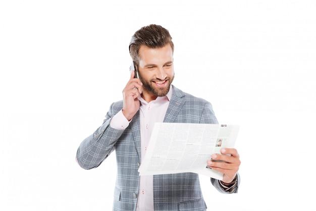 Jovem feliz segurando a gazeta e falando pelo celular