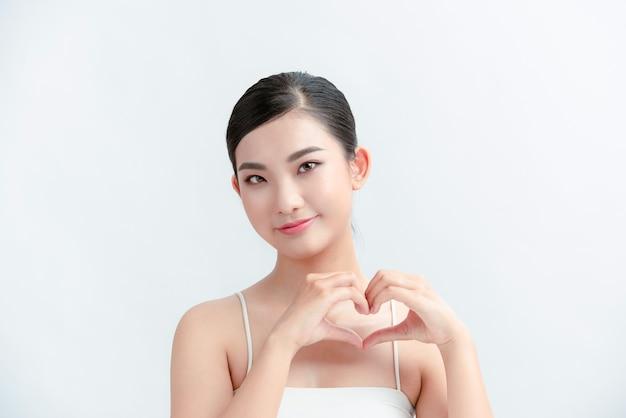 Jovem feliz segurando as mãos em forma de coração perto do peito