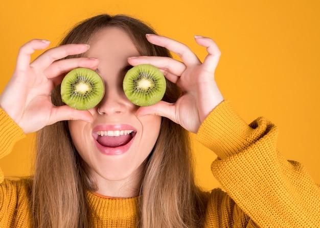 Jovem feliz segurando kiwi cobrindo os olhos, conceito de comida saudável