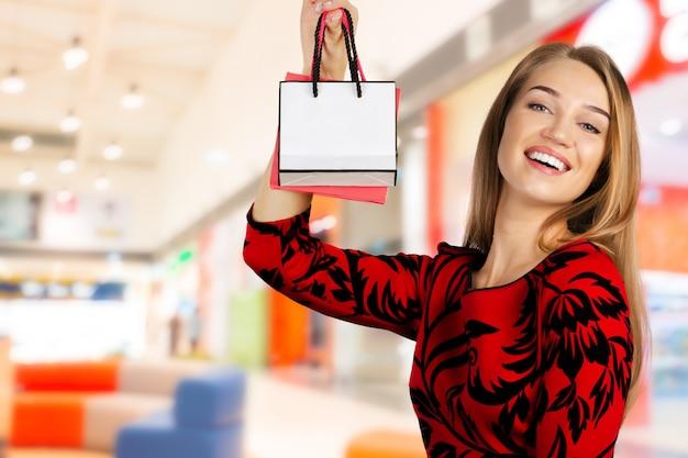 Jovem feliz segurando muitos sacos de compras