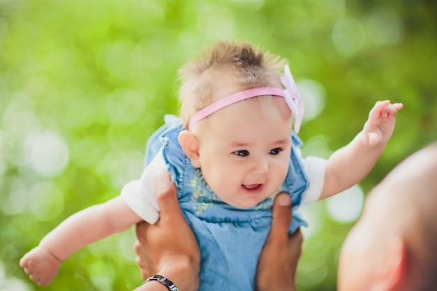 Jovem feliz segurando um bebê sorridente de 2-4 meses de idade em um fundo de folhas não está em foco