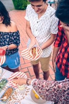 Jovem feliz segurando um cachorro-quente americano em um churrasco de verão ao ar livre com os amigos
