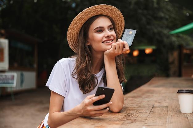 Jovem feliz segurando um cartão de crédito de plástico enquanto usa o telefone celular no café ao ar livre