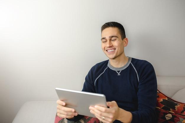 Jovem feliz segurando um tablet digital, sorrindo durante uma videochamada, sentado no sofá em casa