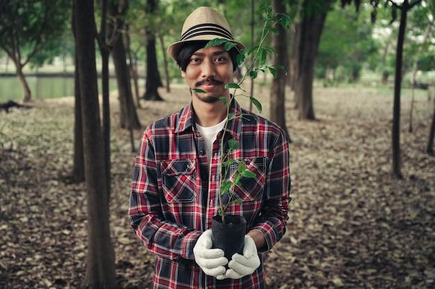 Jovem feliz segurando uma árvore no jardim