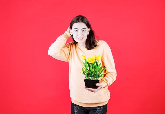 Jovem feliz segurando uma flor natural enquanto raspava a cabeça em um pano de fundo vermelho