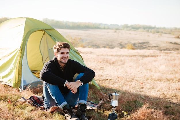 Jovem feliz sentado ao ar livre com uma tenda ao fundo