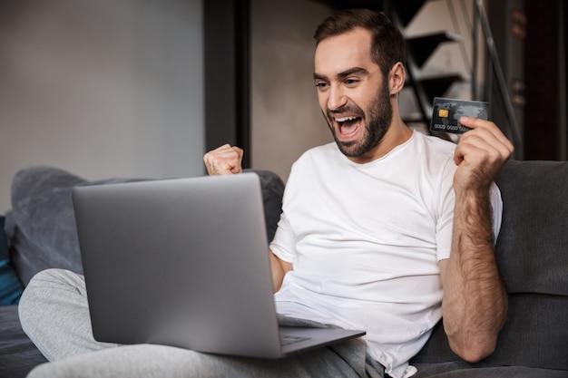 Jovem feliz sentado em um sofá, usando um laptop, comemorando, mostrando um cartão de crédito de plástico