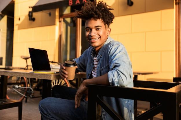 Jovem feliz sentado no café ao ar livre