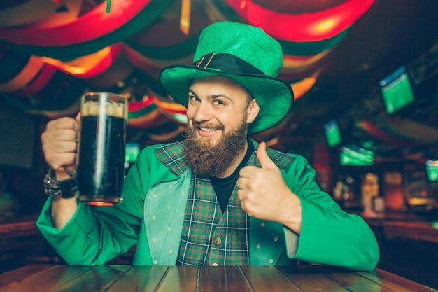 Jovem feliz sentar à mesa no pub e pose. ele segura uma caneca de cerveja preta. cara parece feliz. ele veste o traje de são patrício.