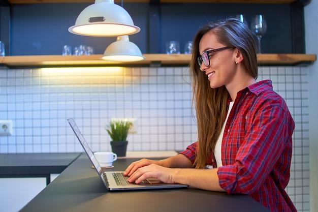 Jovem feliz sorridente fofa casual inteligente de óculos e uma camisa quadriculada trabalhando remotamente online no laptop em uma casa moderna.
