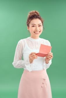 Jovem feliz sorridente mulher asiática, lendo cartão de dia dos namorados isolado sobre fundo verde.