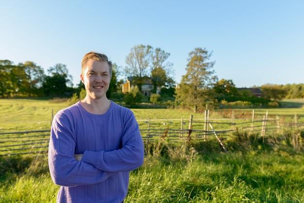 Jovem feliz sorrindo com os braços cruzados em uma planície gramada pacífica com a natureza