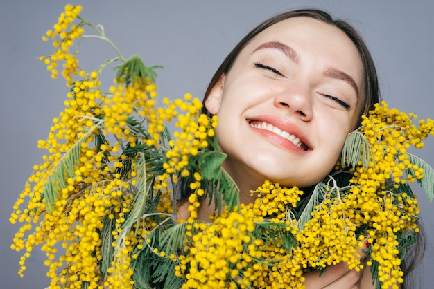Jovem feliz sorrindo, feliz primavera, segurando um grande buquê de mimosa amarela