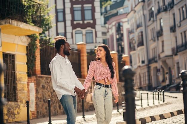 Jovem feliz sorrindo para a namorada enquanto caminhava na rua com ela