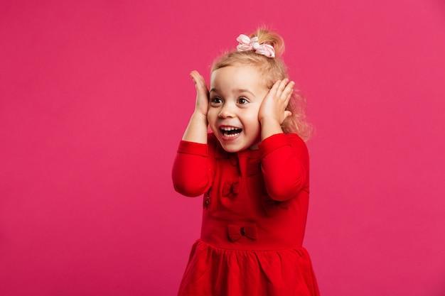 Jovem feliz surpresa no vestido vermelho, segurando sua cabeça