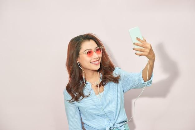 Jovem feliz tirando selfie sobre fundo claro