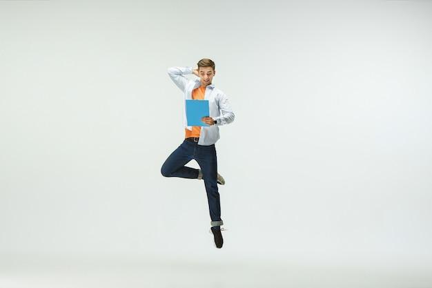 Jovem feliz trabalhando no escritório, pulando e dançando com roupas casuais ou terno isolado no fundo branco.