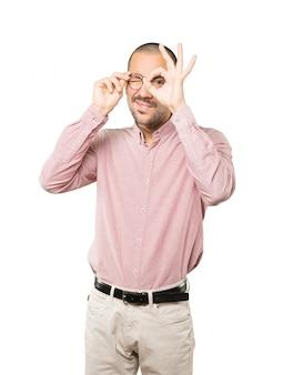 Jovem feliz usando as mãos como um binóculo