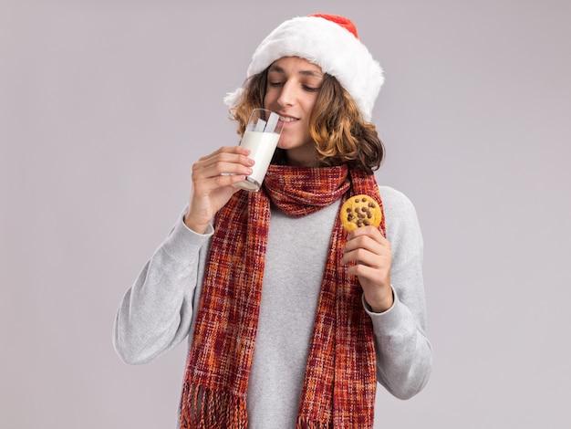 Jovem feliz usando chapéu de papai noel de natal com lenço quente em volta do pescoço, bebendo leite segurando um biscoito
