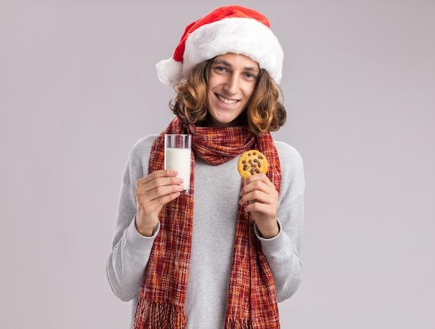 Jovem feliz usando chapéu de papai noel de natal com um lenço quente em volta do pescoço segurando um copo de leite e um biscoito e sorrindo alegremente