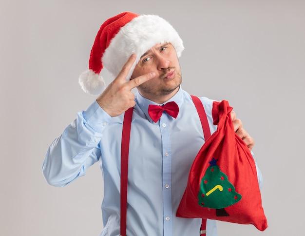 Jovem feliz usando suspensórios gravata borboleta com chapéu de papai noel segurando uma sacola de papai noel cheia de presentes, olhando para a câmera mostrando o sinal v em pé sobre um fundo branco