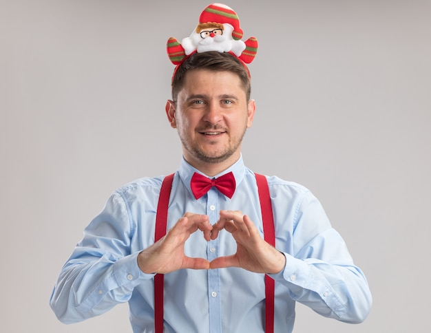 Jovem feliz usando suspensórios gravata borboleta na borda com o papai noel olhando para a câmera fazendo um gesto de coração com os dedos sorrindo alegremente em pé sobre um fundo branco