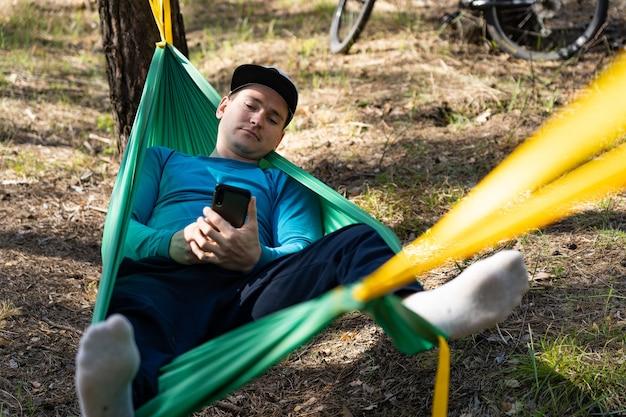 Jovem feliz usando telefone celular com chapéu e relaxando do lado de fora em uma rede na floresta