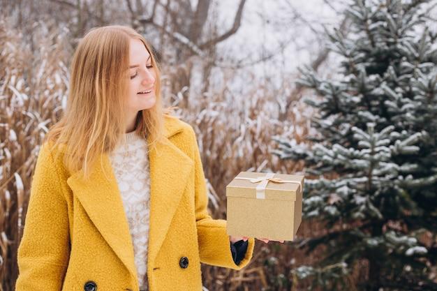 Jovem feliz vestindo um casaco segurando uma caixa de presente de natal perto da natureza