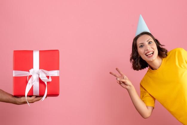 Jovem fêmea aceitando o presente do macho na rosa Foto gratuita