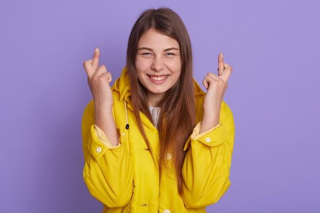 Jovem fêmea acreditando que os sonhos se tornam realidade, esperançosa mulher atraente se sente com sorte, cruza os dedos, sorri amplamente, usa uma jaqueta amarela, posando contra uma parede lilás.