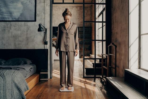Jovem fêmea adorável em um pijama de cetim confortável em pé em balanças eletrônicas no quarto, depois de acordar no início da manhã, antes de tomar um banho refrescante. conceito de perda de peso e estilo de vida saudável