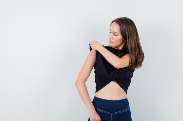 Jovem fêmea ajustando a manga da blusa em blusa preta, calça e parecendo bem arrumada