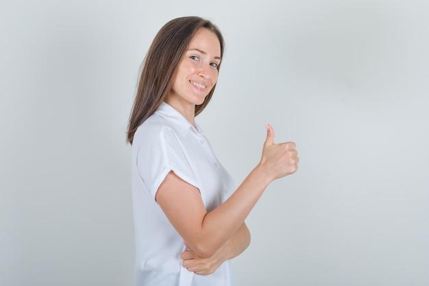 Jovem fêmea aparecendo o polegar na camisa branca e parecendo satisfeita.