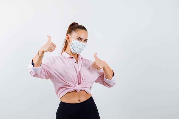 Jovem fêmea aparecendo polegares em camisa, calça, máscara médica e parece feliz. vista frontal.