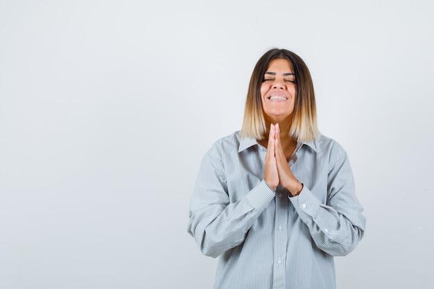 Jovem fêmea aperta as mãos juntas para orar em uma camisa grande e parecendo feliz, vista frontal.