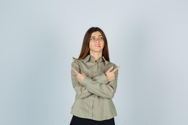 Jovem fêmea apontando para a direita e para a esquerda, mordendo o lábio, olhando para cima na camisa, saia e parecendo esquecida, vista frontal.