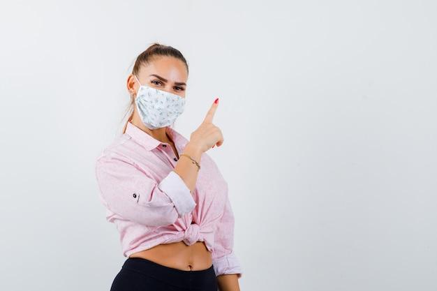 Jovem fêmea apontando para cima em camisa, calça, máscara médica e parecendo confiante. vista frontal.