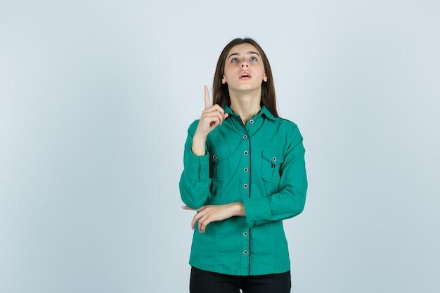 Jovem fêmea apontando para cima em camisa verde e olhando maravilhada, vista frontal.