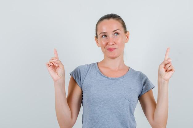 Jovem fêmea apontando para cima em t-shirt cinza e parecendo um sonho, vista frontal.