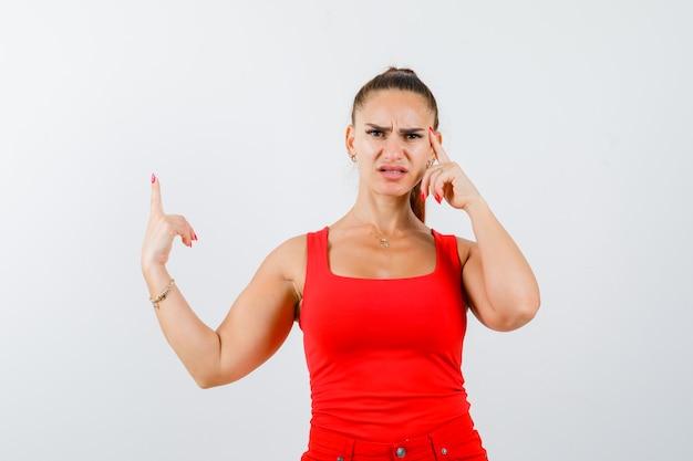 Jovem fêmea apontando para cima em um top vermelho, calças e olhando pensativa. vista frontal.
