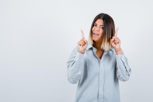Jovem fêmea apontando para cima em uma camisa grande e olhando feliz, vista frontal.