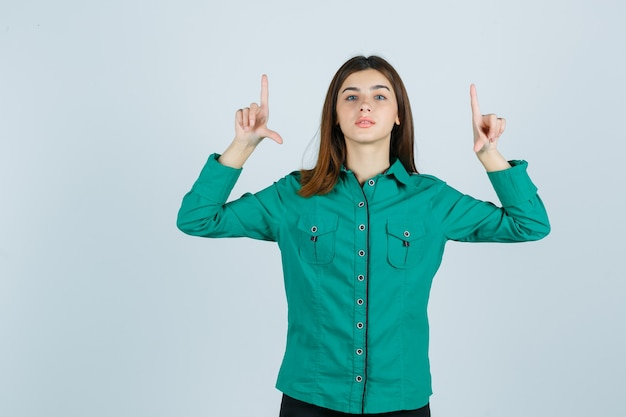 Jovem fêmea apontando para cima em uma camisa verde e olhando confiante, vista frontal.