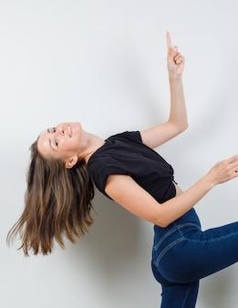 Jovem fêmea apontando para cima enquanto levanta a perna em blusa e calça pretas e parece enérgica