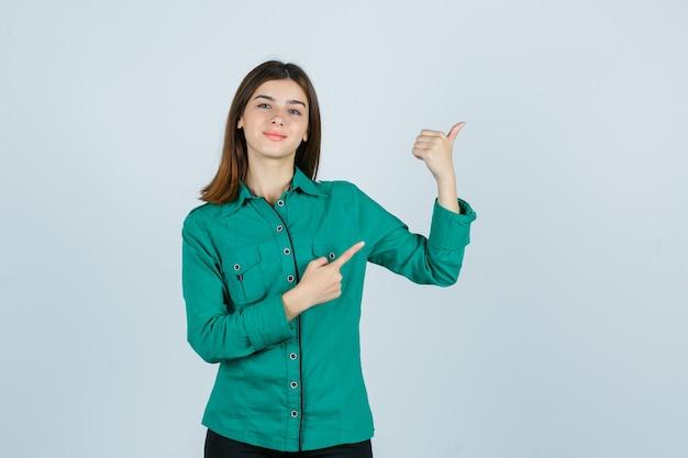 Jovem fêmea apontando para o canto superior direito de camisa verde e olhando alegre, vista frontal.