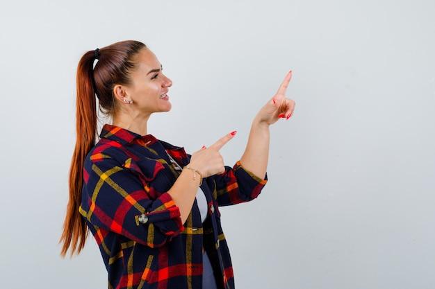 Jovem fêmea apontando para o canto superior direito no topo da cultura, camisa quadriculada e parecendo feliz, vista frontal.
