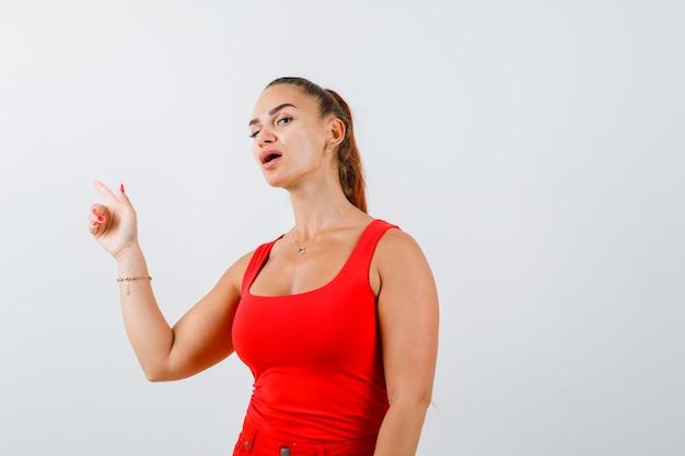 Jovem fêmea apontando para o canto superior esquerdo em uma blusa vermelha, calça e parecendo confusa, vista frontal.
