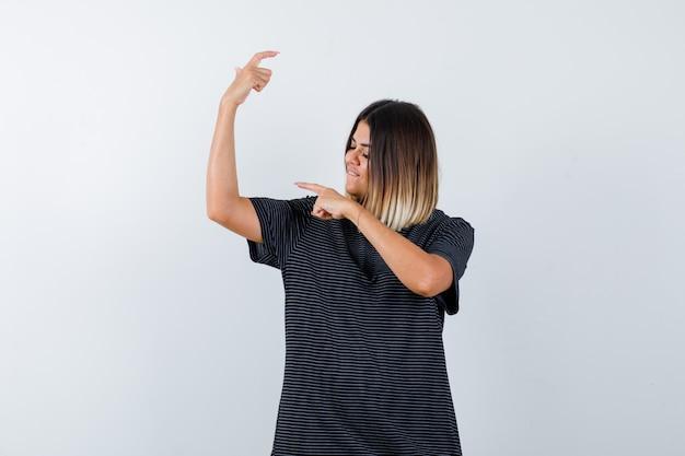 Jovem fêmea apontando para os músculos do braço em vestido polo e parecendo orgulhosa. vista frontal.