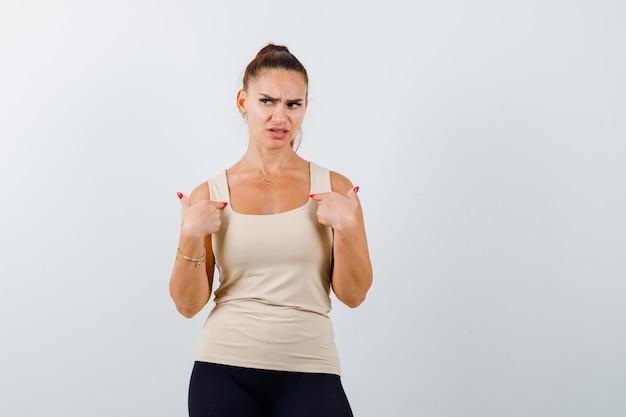 Jovem fêmea apontando para si mesma em um top bege e parecendo estressado, vista frontal.